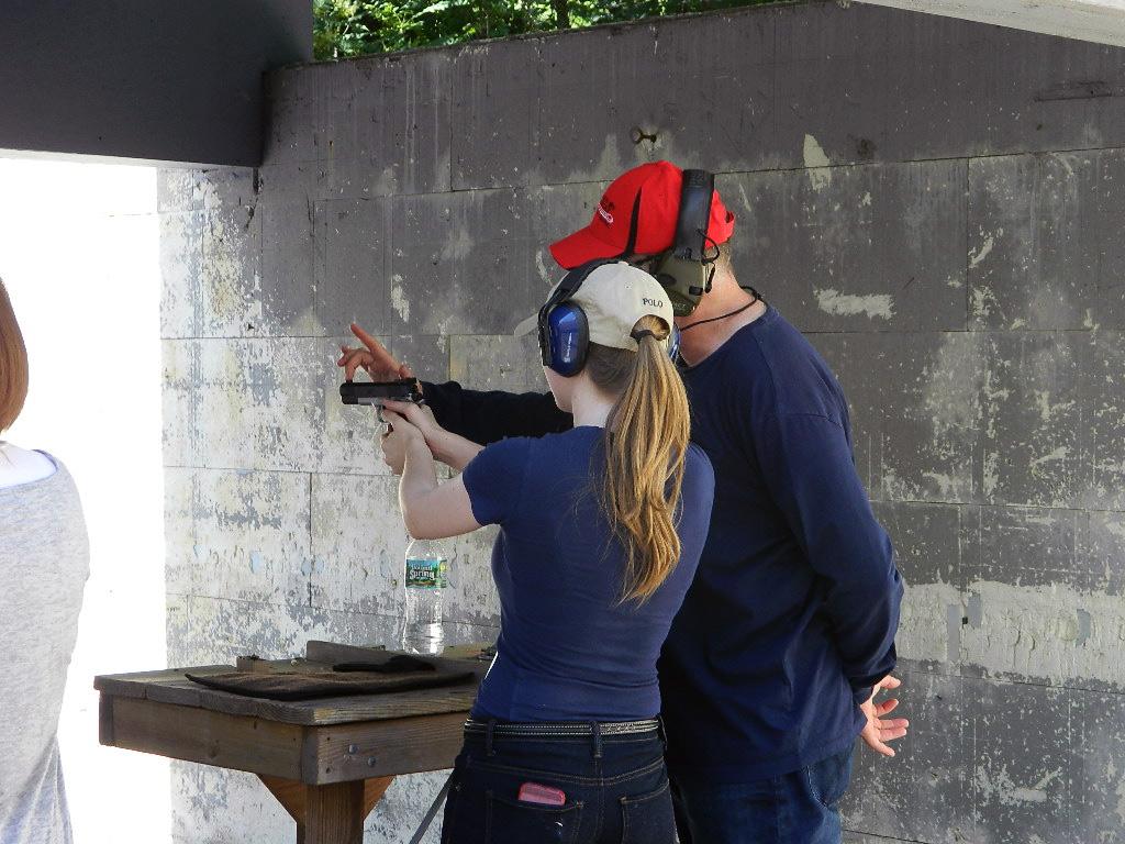 Training a teenager to shoot a handgun.
