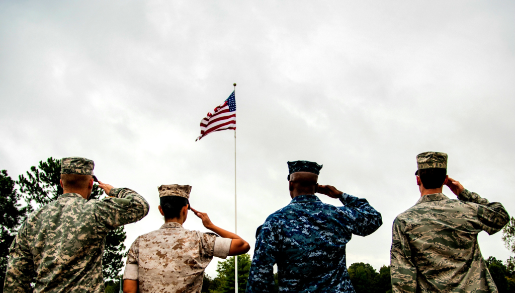 Representatives from each branch of US armed forces soluting American flag