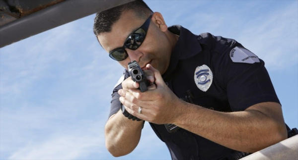 Police officer pointing gun in the direction of viewer