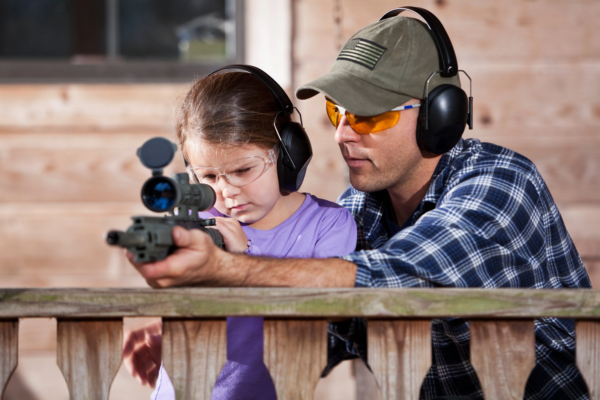 Adult teaching child to shoot rifle