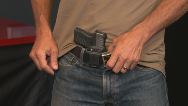 Man carrying concealed pistol in belt holster