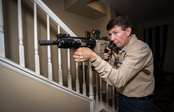 Man defending home with rifle