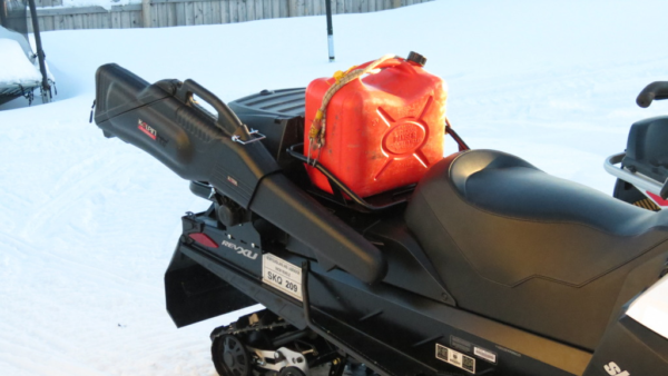 Rifle in case on back of snowmobile