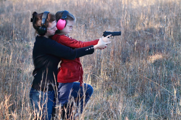 Women teaching girl to shoot pistol