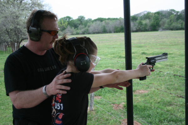 man teaching girl to shoot revolver