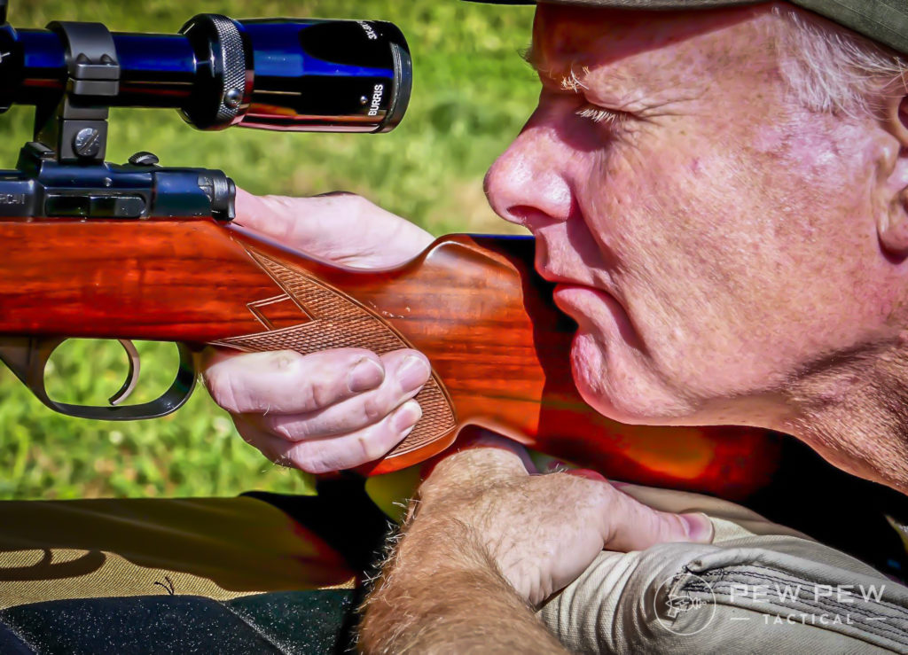 Squeezing your rear bag to adjust your hight and aim while also giving yourself a solid shooting rest.