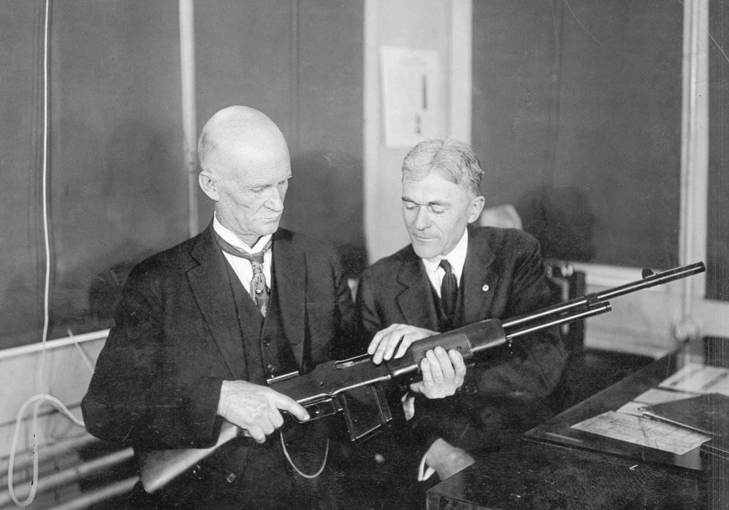 John Moses Browning (left) inspecting a Browning Automatic Rifle (BAR) at the Winchester Repeating Arms Company factory, c. 1918.