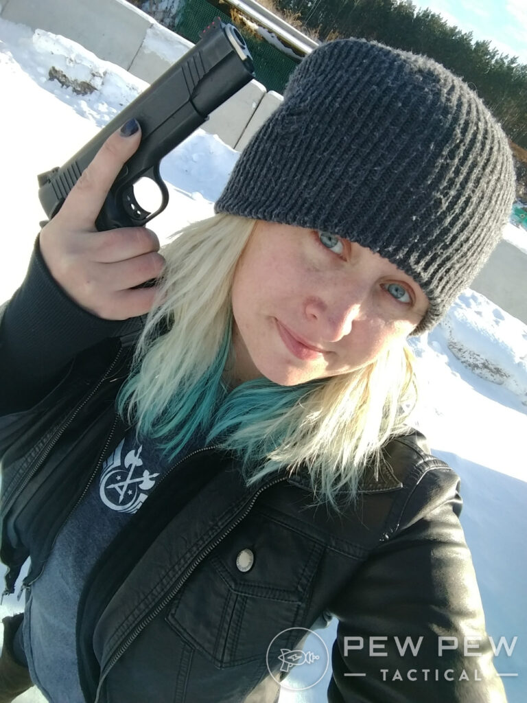 Kat in a beanie with a pistol